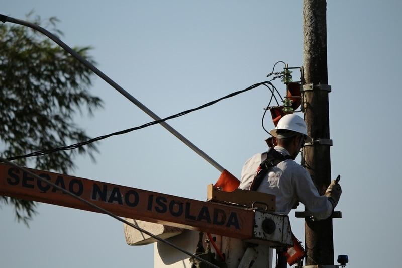 Un trabajador de Duke Energy asistiendo cables eléctricos.
