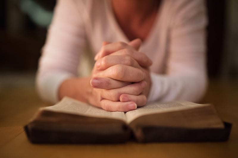 Mujer orando con una Biblia abierta.