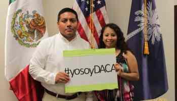 """Dos jóvenes con una pancarta """"Yo Soy DACA"""""""