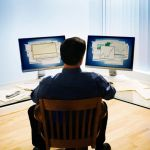 Man using Dual Computer Screens