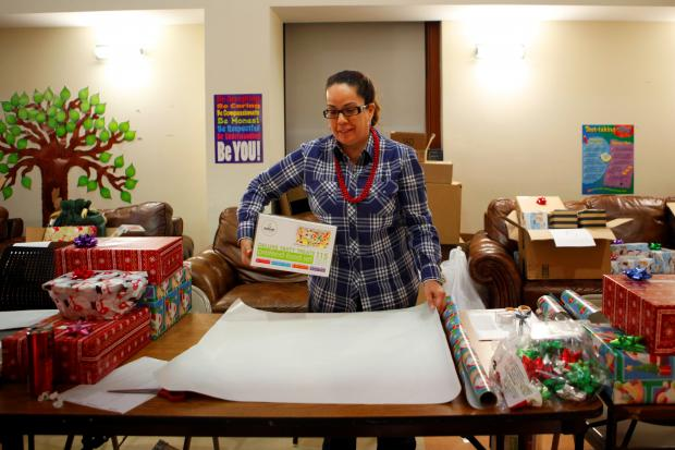 A staff member wraps gifts donated for children during Lantern's annual holiday gift drive