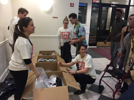 Volunteers from Maple food delivery service hand our free socks to Lantern residents