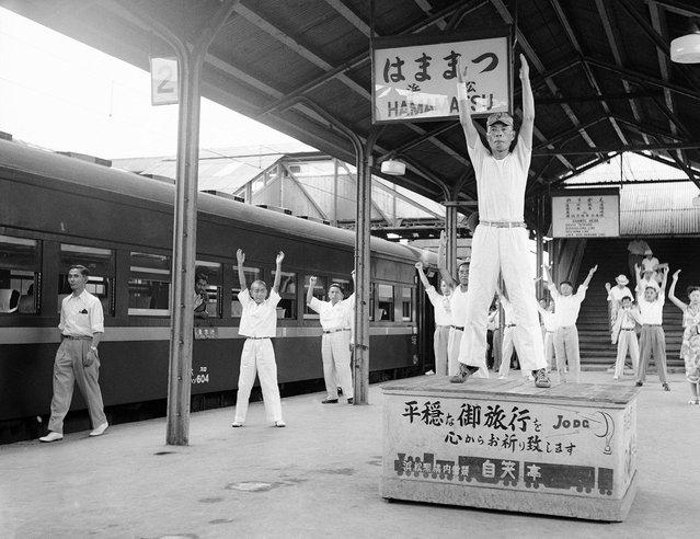 Para penumpang di sebuah kereta api dari Tokyo menuju Osaka tampak mengikuti senam selama tiga menit di bawah bimbingan seorang instruktur, dalam sebuah persinggahan selama lima menit di Hamamatsu, 27 Agustus 1952. Layanan yang tidak biasa ini diadakan untuk membantu para penumpang dalam perjalanan jauh untuk melemaskan otot-otot mereka di stasiun yang merupakan setengah perjalanan diantara Tokyo dan Osaka. Dalam senam ini, disediakan musik untuk senam, dan bahkan sebuah panggung untuk sang instruktur. (Photo by Max Desfor/AP Photo via The Atlantic)