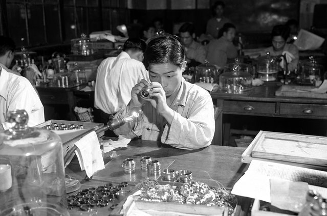 Sebuah lensa sedang diperiksa di pabrik kamera Nikon di Tokyo, 5 Januari 1952. (Photo by Bob Schutz/AP Photo via The Atlantic)