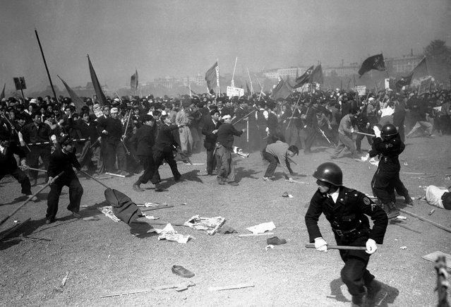 "Para demonstran pro-komunis melempari polisi Jepang dengan batu pada kerusuhan ""May Day"" di Tokyo pada 1 Mei 1952. Korban berjatuhan dari kedua pihak, polisi Jepang menggunakan gas air mata, senapan, dan pentungan untuk memukul mundur para perusuh. (Photo by Max Desfor/AP Photo via The Atlantic)"