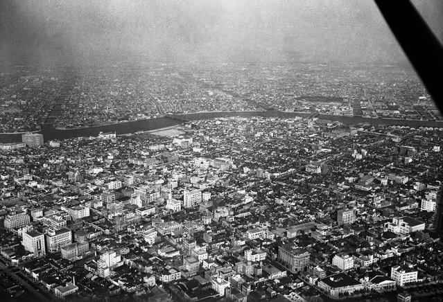 Sebuah area di Tokyo, terlihat dari langit pada 5 Agustus 1955. Bangunan-bangunan modern telah menghapus bekas reruntuhan blok-blok yang telah diratakan dengan tanah. Sungai Sumida mengalir dengan damai melalui distrik Hamacho dan distrik Fukawaga. Rumah-rumah grosir dan gudang-gudang memenuhi sebagian besar distrik ini. (Photo by AP Photo via The Atlantic)