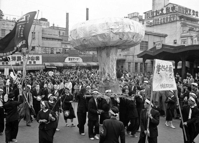 Sebuah replika raksasa dari sebuah awan jamur bom Hiroshima diarak sepanjang jalan di Tokyo, Jepang, pada 1 Mei 1957, dalam sebuah aksi memprotes rencana uji coba bom atom Inggris di Pulau Christmas. (Photo by AP Photo via The Atlantic)