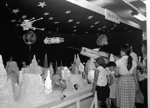 Para anak-anak Jepang ini dengan antusias melihat pameran luar angkasa di sebuah department store di Tokyo, pada 19 Agustus 1958. Mereka melihat sebuah roket yang mendarat di permukaan bulan, makhluk-makhluk aneh, bahkan satelit yang mengitari bulan. n, strange looking people of the moon walking around, and even a satellite going around the moon. (Photo by AP Photo via The Atlantic)