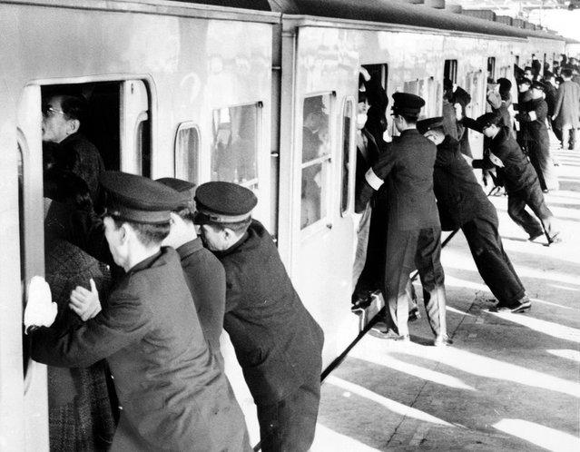 "Para mahasiswa yang bekerja sebagai ""petugas pendorong"" mendesakkan para penumpang ke dalam kereta komuter di Tokyo. (Photo by Library of Congress via The Atlantic)"