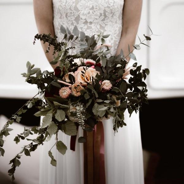 mariée avec son bouquet devant une caravane
