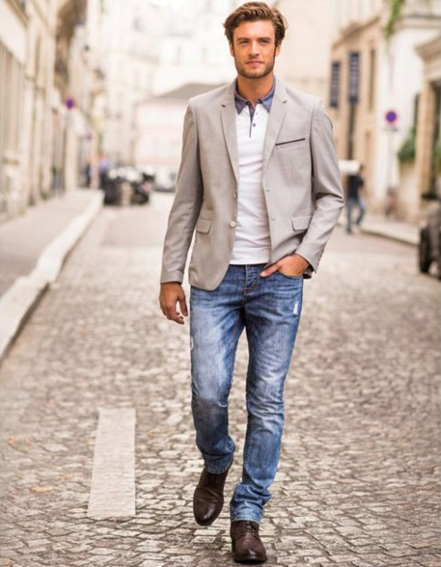Il porte un jean délavé, un polo blanc et une veste habillée couleur gris / beige.