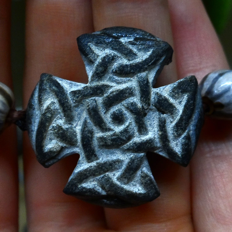 Entrelac en relief sur très petit galet taillé en forme de croix
