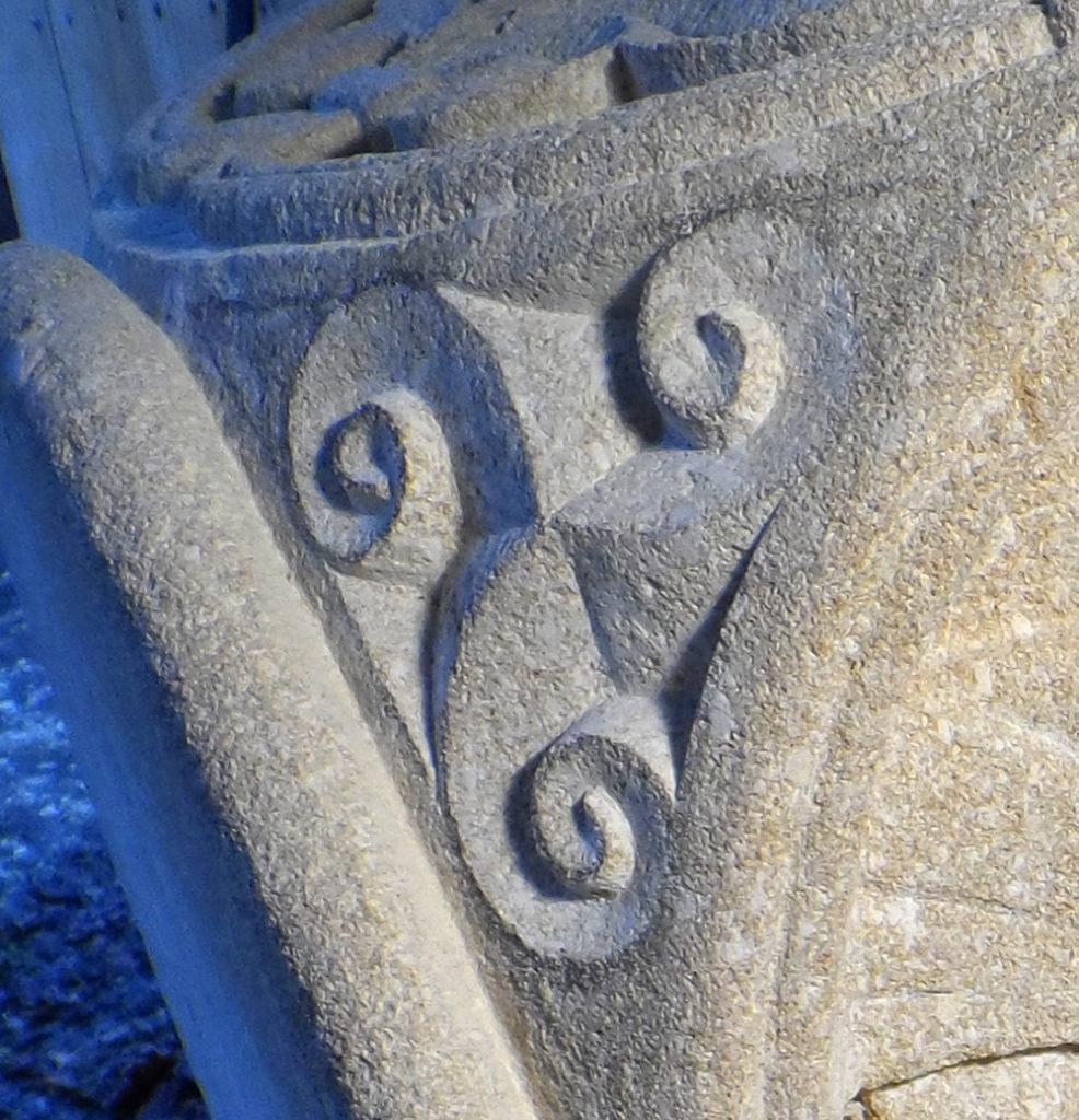 Triscèle gravé sur un angle de chapiteau en calcaire tendre