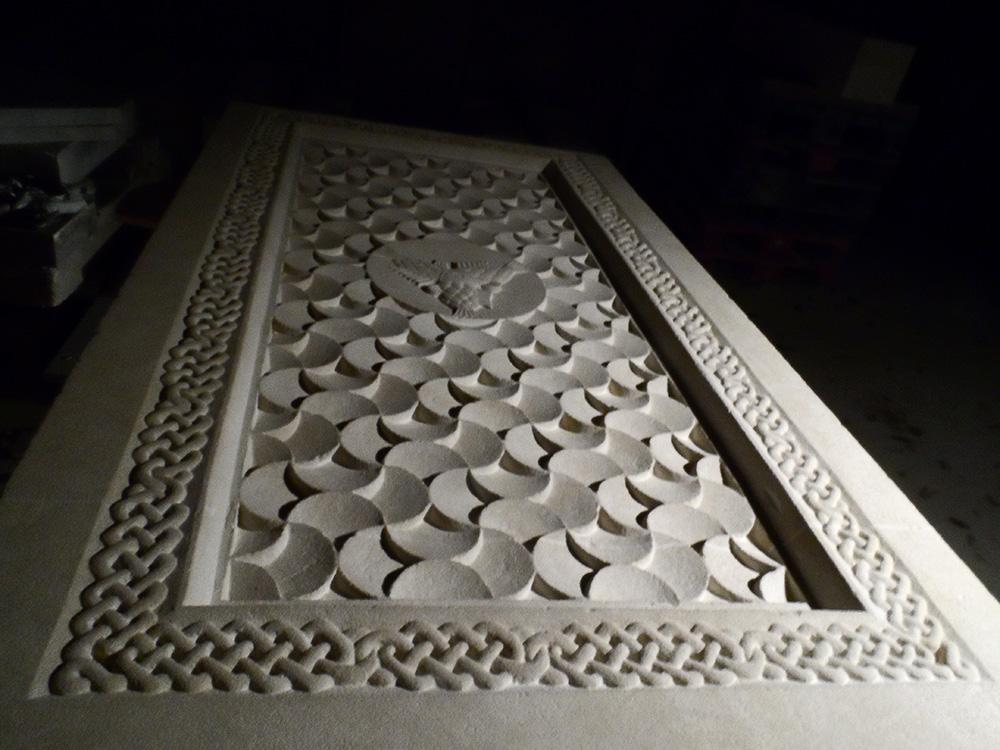 Grande plaque de saint maximin ornée d'une bordure avec des entrelacs et un motif gravé se répétant à l'intérieur, sauf au centre où 3 poissons réunis par la même tête au centre apparaissent.