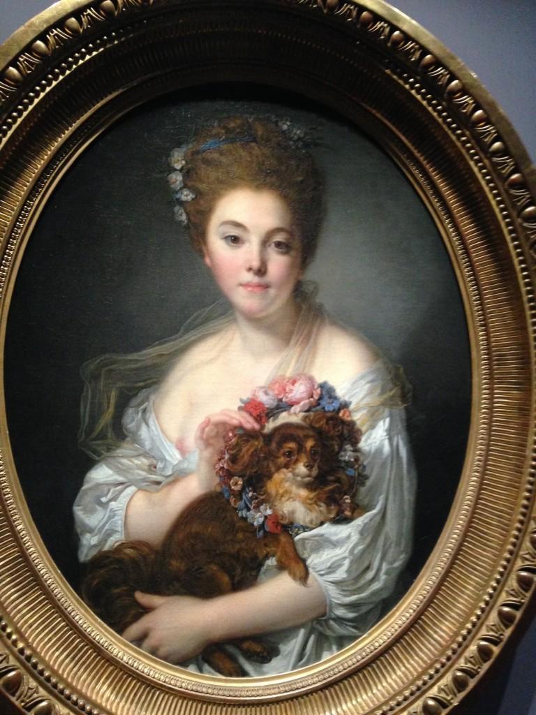 """Jean-Baptiste Greuze, Jeune femme couronnant de fleurs un petit épagneul noir, dite """"Madame de Porcin"""" vers 1770, huile sur toile de forme ovale, 72x57cm, © Musée des Beaux-Arts d'Angers"""