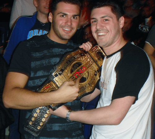 Mike and Jim Fusco holding one of the TNA Tag Team Championship belts.