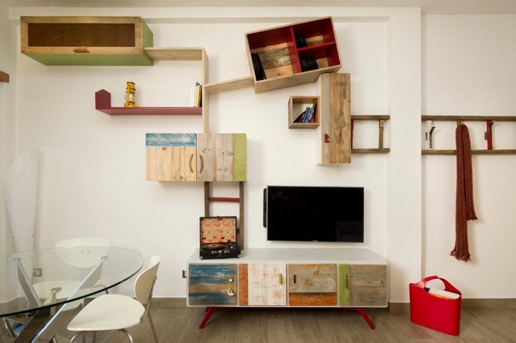Parete attrezzata Ginevra in legno di recupero, con vecchi oggetti tra cui una scala in legno.