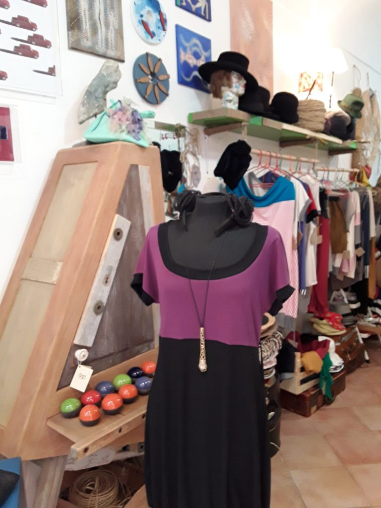 Vestito cucito a mano con manica corta viola e nero e mobile artigianale in legno massello e cassettini