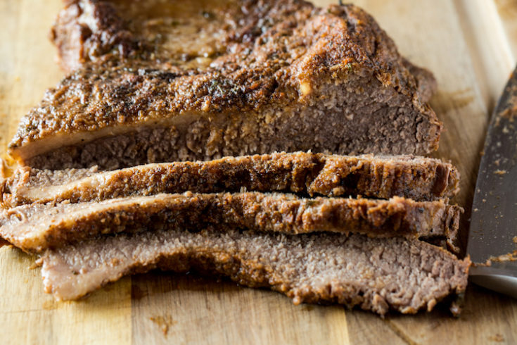close up image of sliced cooked beef brisket on a wood cutting board
