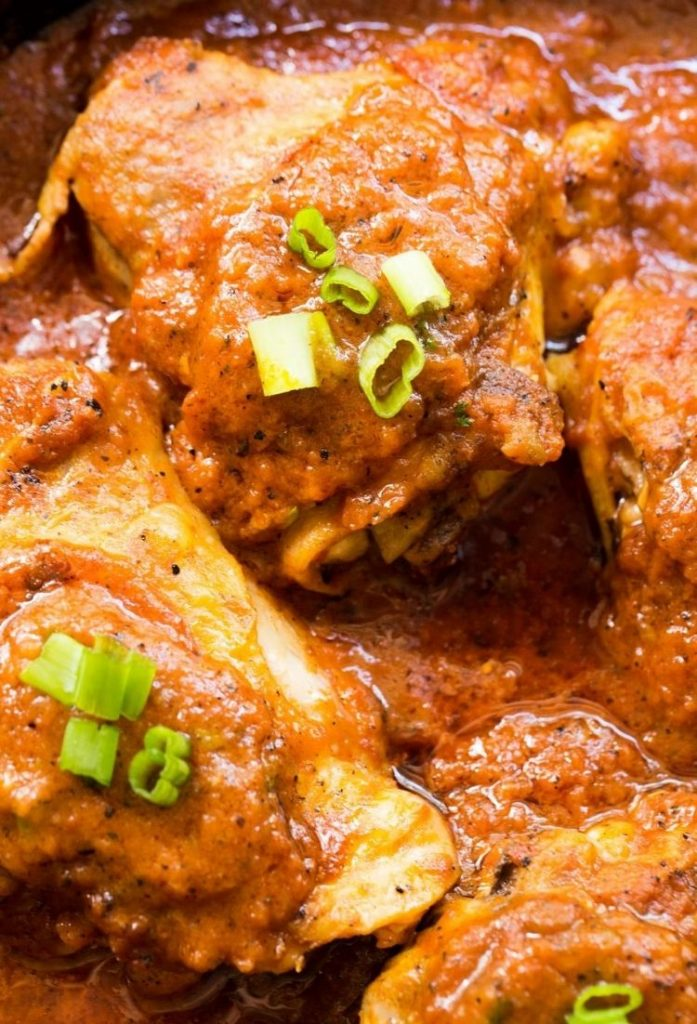 chicken in a pan surrounded and covered in a red sauce