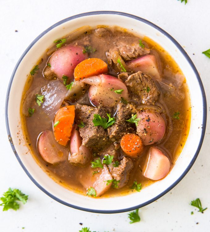 low carb crockpot beef stew in a white bowl with blue rim on a white background