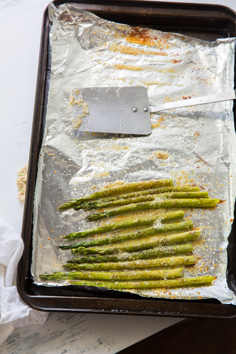 roasted garlic parmesan asparagus on a cookie sheet with aluminum foil and a spatula