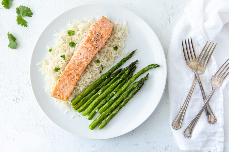 baked salmon on a bed of white rice with baked asparagus