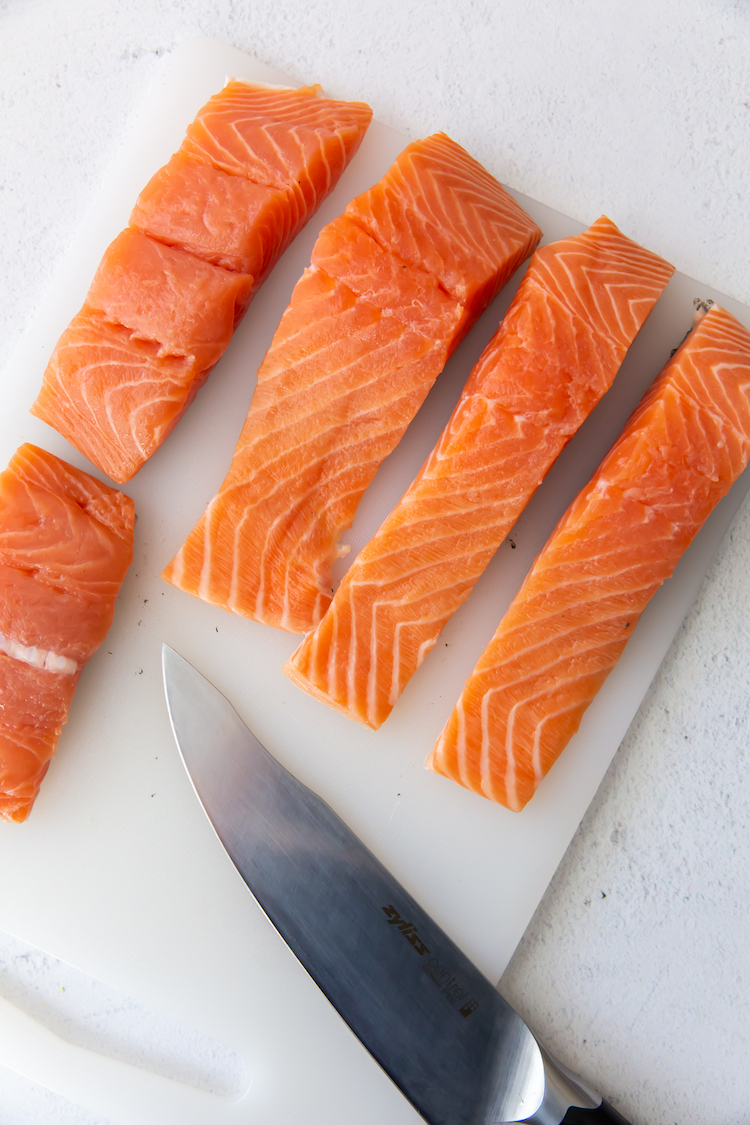 salmon filets on a cutting board with a knife