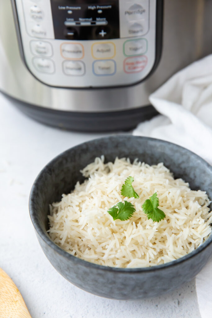 blue bowl filled with basmati rice topped with cilantro