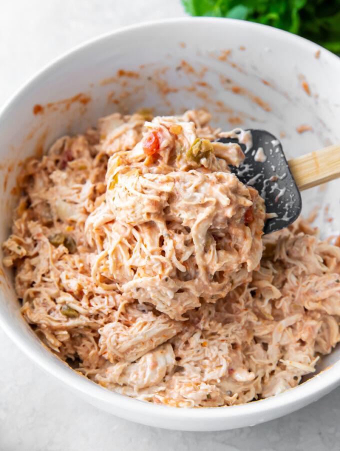 creamy salsa chicken recipe in a while bowl with a spatula