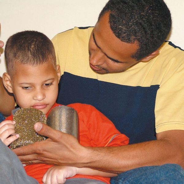 Menino de aproximadamente 4 anos, cabelos escuros e curtos. Está sentado e segura o Chocalho ouro-prata com a mão direita, com a mediação do pai, posicionada atrás dele.