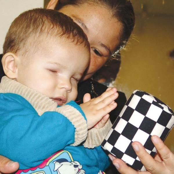 Bebê de aproximadamente 1 ano, com as mãos unidas em linha média. Está no colo da mãe, posicionada atrás dele. Com a mão esquerda, ela apresenta o Chocalho Sensorial.