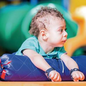Menino de aproximadamente 1 ano, cabelos claros e cacheados, está de bruços, com apoio do Rolinho, na altura do peito.