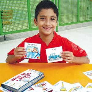 Sentado em frente à uma mesa amarela, um menino de aproximadamente 10 anos, cabelos escuros, curtos e sorriso no rosto, segura um cartão com a mão esquerda e outro com a direita.