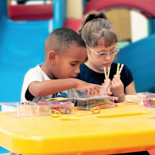 Um menino e uma menina de aproximadamente 5 anos, sentados em frente à uma mesa amarela. O menino está com a mão sobre a caixinha de plástico e ao lado dele, a menina tem nas mãos, dois pregadores de plástico.