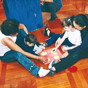 Duas crianças estão sentadas no chão, com o apoio de duas mulheres, posicionadas atrás deles. Á frente deles, a prancheta do brinquedo Para Classificar. As mediadoras estão com as mãos sobre as mãos das crianças.
