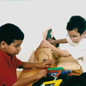Dois meninos de aproximadamente 5 anos, estão sentados em frente à uma mesa de madeira, onde está o brinquedo Trincos e Truques, com as mãos sobre alguns dos objetos do brinquedo.