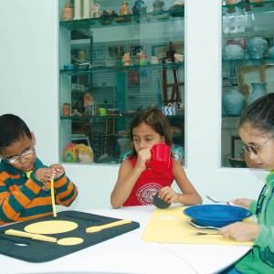 Duas meninas e um menino sentados ao redor de uma mesa branca. Da esquerda para a direita, menino em frente à prancha de alimentação azul; menina com caneca vermelha na mão direita; menina em frente ao prato azul, sob prancha de alimentação amarela.