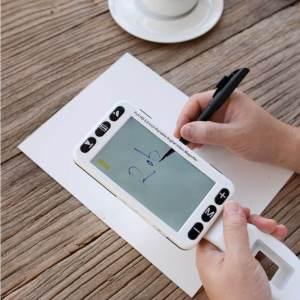 Uma pessoa usando a lupa eletrônica portátil uemax 5 como apoio para assinar um documento impresso