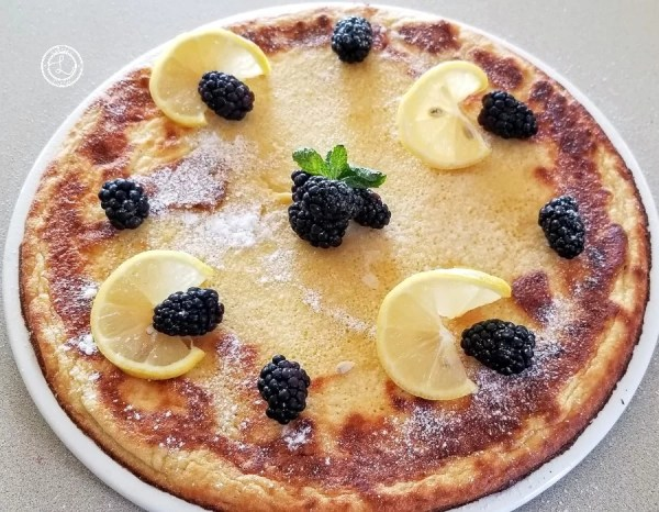Dutch Pancake on a large serving plate with lemon slices, blackberries, and mint
