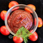 Refined Sugar-Free Homemade Ketchup in a bowl surrounded by tomatoes and a sprig of dill.