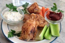 Chicken Wings on a plate with celery, carrots, and ranch.
