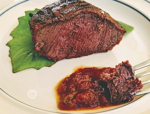 LaRenas Corner Steakhouse Sauce: Steak on a plate with a bite of steak in steak sauce.