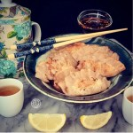 A bowl of potstickers, with lemon wedges, tea cups, teapot and chopsticks.