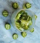 Bread and butter pickles in a bowl surrounded by pickles