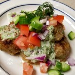 Greek Turkey Meatballs on a plate with chopped red onions, tomatoes, and cucumber.
