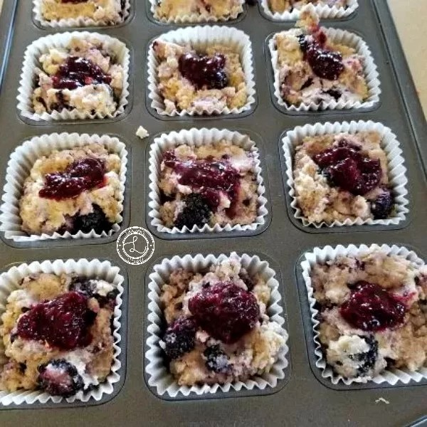 Muffins with homemade jam going in the oven