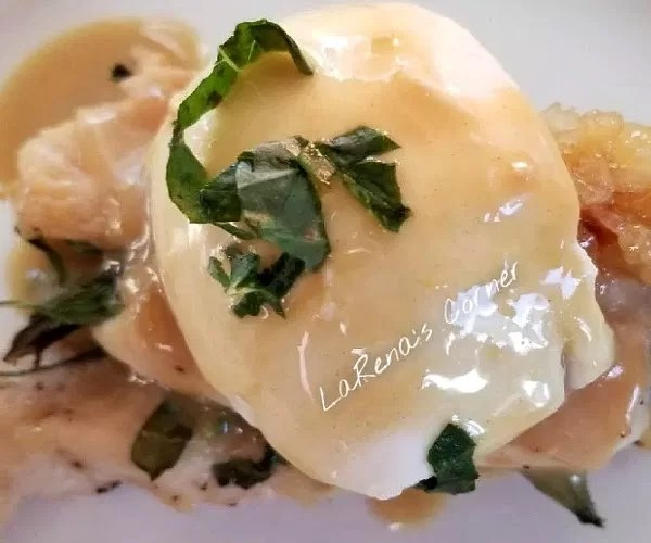 Cooked chicken decorated with a slice of melted mozzarella, maple mustard sauce and chiffonade basil