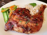 A chicken quarter with cucumber salad and rice.