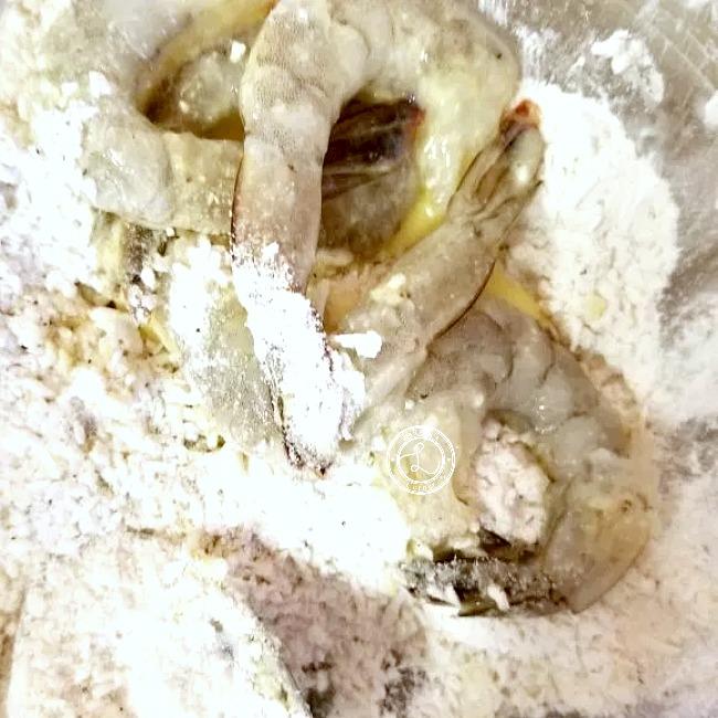 Dipping dipped shrimp into flour mixture